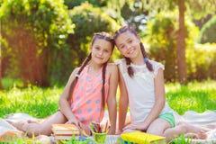 Deux filles assez petites lisant en parc Photographie stock