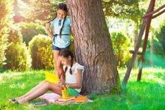 Deux filles assez petites lisant en parc Photo libre de droits