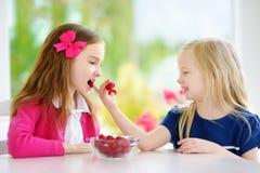 Deux filles assez petites mangeant des framboises à la maison Enfants mignons appréciant leurs fruits et baies organiques frais s Photo libre de droits