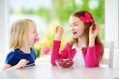 Deux filles assez petites mangeant des framboises à la maison Enfants mignons appréciant leurs fruits et baies organiques frais s Photos libres de droits