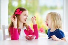Deux filles assez petites mangeant des framboises à la maison Enfants mignons appréciant leurs fruits frais et baies sains Image stock