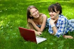 Deux filles attirantes avec un ordinateur portatif en stationnement Photo stock