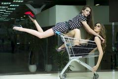Deux filles attirantes dans le chariot à achats Photos libres de droits