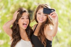 Deux filles attirantes de métis faisant Selfies avec Smartphone Images stock