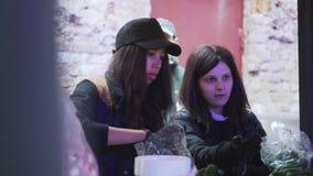 Deux filles attirantes portant le chapeau et les vêtements foncés assortissent les légumes verts banque de vidéos