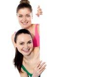 Deux filles attirantes retenant le whiteboard blanc Images libres de droits