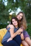 Deux filles attirantes s'asseyant l'un à côté de l'autre dans la chaise, smilin Photo libre de droits