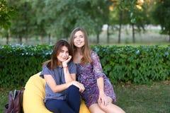 Deux filles attirantes s'asseyant l'un à côté de l'autre dans la chaise, smilin Photographie stock libre de droits