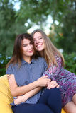 Deux filles attirantes s'asseyant l'un à côté de l'autre dans la chaise, smilin Image stock