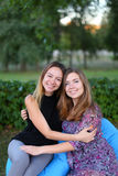 Deux filles attirantes s'asseyant l'un à côté de l'autre dans la chaise, smilin Images stock