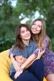 Deux filles attirantes s'asseyant l'un à côté de l'autre dans la chaise, smilin Images libres de droits