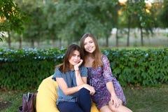 Deux filles attirantes s'asseyant l'un à côté de l'autre dans la chaise, smilin Photos stock