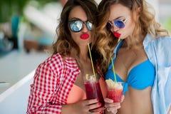 Deux filles attirantes se reposant sur la barre de plage, boivent un cocktail régénérateur, riant et ayant l'amusement Se baigner photos libres de droits