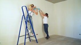 Deux filles au chantier de construction colle le papier peint au mur banque de vidéos
