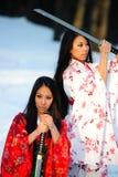 Deux filles au sujet d'une épée dans des mains photographie stock