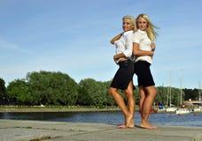 Deux filles aux pieds nus sur le côté de fleuve Images stock