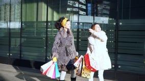 Deux filles avec des achats dans leurs mains se tiennent sur la rue pr?s de la fen?tre de magasin banque de vidéos