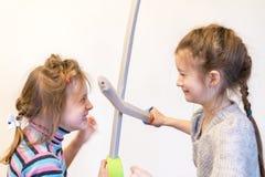 Deux filles avec des chevaliers de jeu d'épées de jouet Deyochki discutent et deviennent fâché Conflit Photo stock