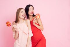 Deux filles avec des lollypops sur le fond rose célébrant femmes jour le 8 mars images libres de droits