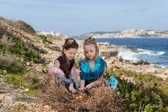 Deux filles avec des nids de cheveux et robes d'oiseau regardant des oeufs dans un grand nid Photos libres de droits
