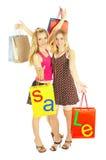Deux filles avec des sacs - achats de comparaison. Vente ! Photo libre de droits