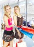 Deux filles avec des sacs - achats de comparaison. Vente ! Photo stock