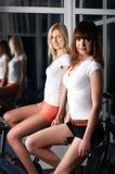 Deux filles avec du charme dans une salle de gymnastique Photographie stock libre de droits