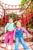Deux filles avec du charme sur le filet du terrain de jeu Photos stock