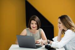 Deux filles avec l'ordinateur portable à la table Photo libre de droits