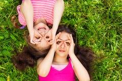 Deux filles avec la forme ronde de mains sur le visage Photos stock