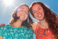 Deux filles avec le ciel bleu et la lumière du soleil à l'arrière-plan Image stock