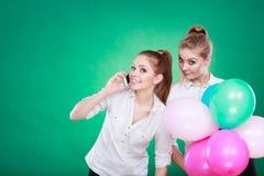 Deux filles avec le téléphone portable et les ballons Image libre de droits