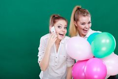 Deux filles avec le téléphone portable et les ballons Photos stock