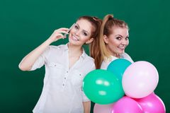 Deux filles avec le téléphone portable et les ballons Photographie stock