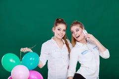 Deux filles avec le téléphone portable et les ballons Image stock