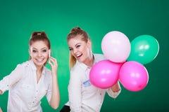 Deux filles avec le téléphone portable et les ballons Images stock