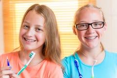 Deux filles avec les arrêtoirs dentaires brossant des dents photographie stock
