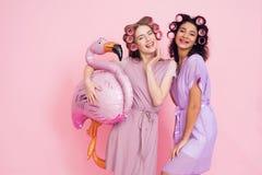 Deux filles avec les bigoudis de cheveux et le baloon rose de flamant Ils célèbrent des femmes ` s jour le 8 mars Photographie stock libre de droits