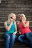 Deux filles avec les téléphones Photographie stock libre de droits