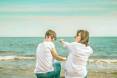 Deux filles avec leurs dos vers la mer Photo stock