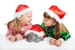 Deux filles avec un lapin dans des capuchons de Santy Image stock