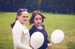 Deux filles avec un regard sévère et des ballons Photo libre de droits