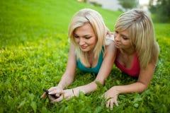 Deux filles avec un téléphone portable se trouvant sur l'herbe Photographie stock libre de droits