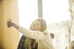 Deux filles ayant l'amusement tout en buvant du café Image libre de droits