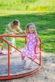 Deux filles balançant sur le terrain de jeu Images libres de droits