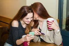 Deux filles bavardant dans une barre de café Photos stock