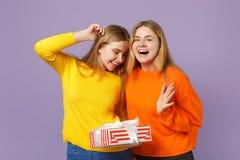 Deux filles blondes étonnées de soeurs de jumeaux dans des vêtements vifs tiennent la boîte actuelle rayée rouge avec le ruban de image libre de droits