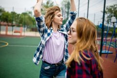Deux filles blondes assez de sourire utilisant les chemises à carreaux se tiennent sur le sportsfield et ont l'amusement Sport et images stock