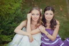 Deux filles blondes de dame d'yeux bleus de brune d'amies de soeurs posant ensemble la soirée de jour ensoleillé d'été se sont ha Photo stock