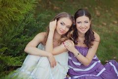 Deux filles blondes de dame d'yeux bleus de brune d'amies de soeurs posant ensemble la soirée de jour ensoleillé d'été se sont ha Photographie stock libre de droits